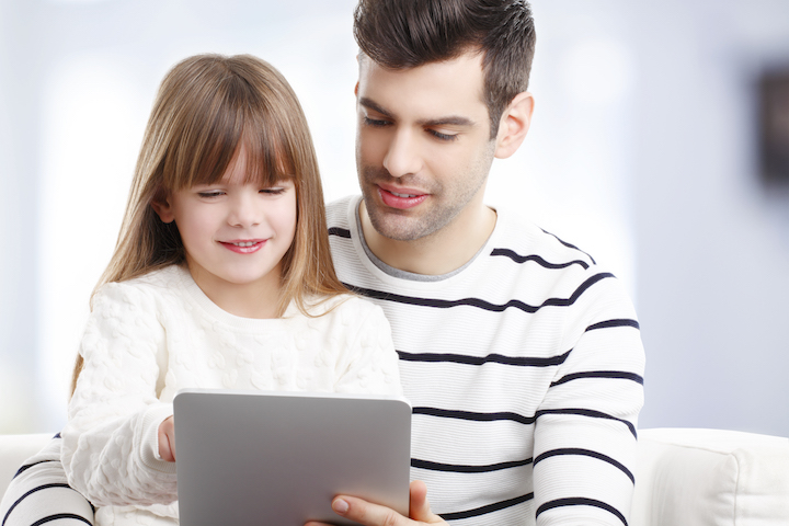 Image of young girl at digital tablet while sitting with her father.