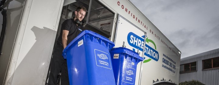 Image of Shred Station operative moving a bin of confidential waste onto an eco-friendly mobile shredding vehicle