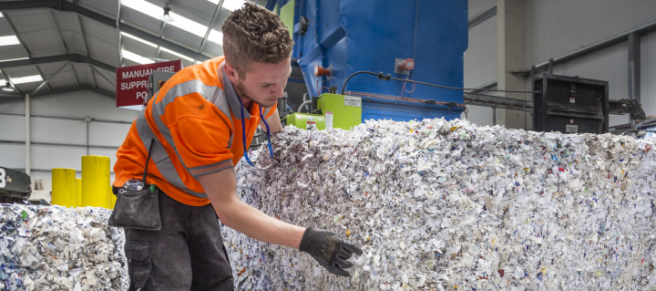 Shred Station employee examining shredded paper