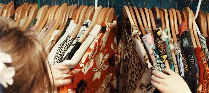 Image of woman looking through garments on a clothing rail