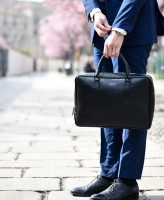 Image of midsection of person in suit holding a briefcase