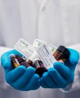 Medical professional holding two handfulls of prescription medication
