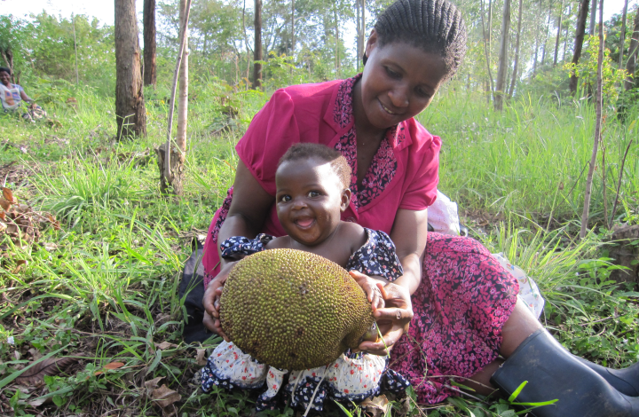 Image of smiling Ugandan mother and her laughing baby daughter while collecting fruit