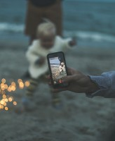 taking photo of child on beach sharenting