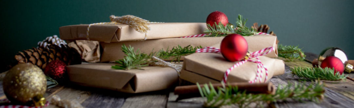Image of presents wrapped in brown recyclable wrapping paper with string and pine